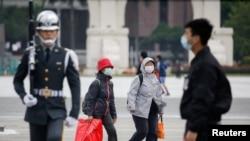 資料照片--遊客在經過台北中正紀念館的升旗儀式時,戴上防護口罩以保護自己免受冠狀病毒病(冠狀病毒)的侵襲。 (2020年3月11日)