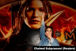 "FILE PHOTO: Student Natchacha Kongudom flashes a three-finger salute inspired by the movie ""The Hunger Games"" in front of a billboard of the film outside the Siam Paragon cinema in Bangkok November 20, 2014."