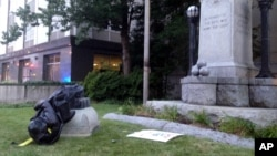 A toppled Confederate statue lies on the ground, Aug. 14, 2017, in Durham, N.C. Activists on Monday evening used a rope to pull down the monument outside a Durham courthouse. The Durham protest was in response to a white nationalist rally held in Charlottesville, Va, over the weekend.