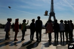 Tourists pose for a souvenir photo on Trocadero with the Eiffel Tower in background on a sunny day in Paris, Thursday, March 30, 2017. France is experiencing heat wave condition with temperatures crossing 22 degrees Celsius (72 Fahrenheit) in several areas.