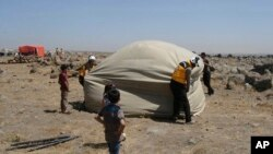 This photo, released by the Syrian Civil Defense White Helmets, shows civil defense workers setting up a tent for civilians who fled from Daraa after shelling by Syrian government forces, in the town of Qunaitra, southwestern Syria, June 28, 2018.