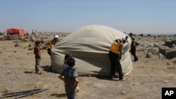 This photo, released by the Syrian Civil Defense, shows the group workers setting up a shelter for civilians who fled from Daraa after shelling by Syrian government forces, in the town of Qunaitra, southwestern Syria, June 28, 2018.