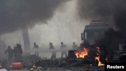 Cư dân dập tắt 1 đám cháy mà các nhà hoạt động cho là do cuộc không kích của quân đội Syria gây ra, ở trung tâm Raqqa, 6/9/2014.