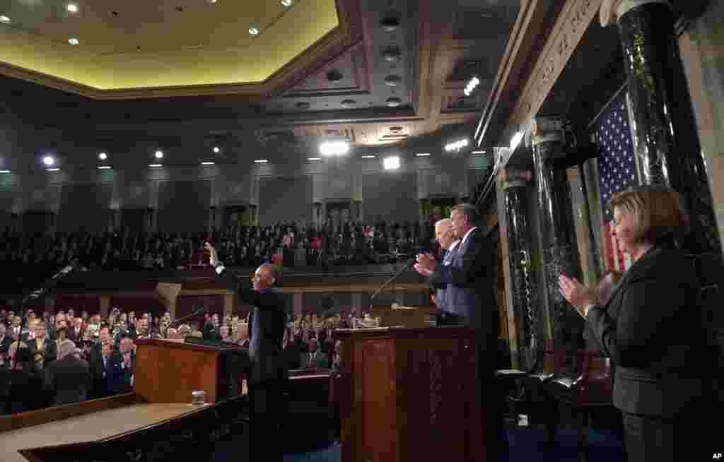 امریکی صدر اوباما ہاتھ ہلا کر شرکاء کا جواب دے رہے ہیں۔