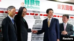 Liberal Democratic Party (LDP) Secretary-General Sadakazu Tanigaki, center left, gestures next to Japan's Prime Minister Shinzo Abe, center right, as they pose during an election night event at the LDP headquarters in Tokyo, Dec. 14, 2014.