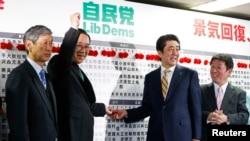 日本首相安倍晋三(中右)等人在选举之夜的活动中