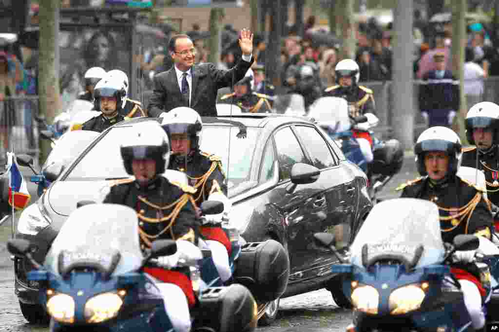 Francois Hollande drives down the Champs Elysees avenue in Paris after the handover ceremony.