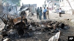 Petugas keamanan Somalia melihat rongsokan bom mobil yang digunakan militan untuk menyerang komplek pengadilan di Mogadishu (14/4).