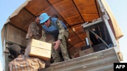 联合国驻南苏丹使团发布的照片显示,维和人员在世界粮食署组织的食品分发活动期间向流离失所者发放食品。(2013年12月22日)