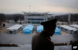 FILE - Korean People's Army Lieutenant Colonel Nam Dong Ho is silhouetted against the truce village of Panmunjom at the Demilitarized Zone (DMZ) which separates the two Koreas.