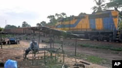 Residents sit near a train pulling carriages with bauxite in Kamsar, Guinea, October 2008. (file photo)