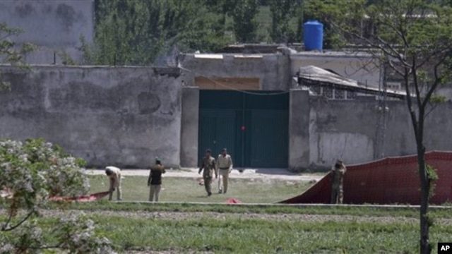 Pakistan army troops remove canvas screens from outside a house, where al-Qaida leader Osama bin Laden was caught and killed in Abbottabad, Pakistan, May 3, 2011