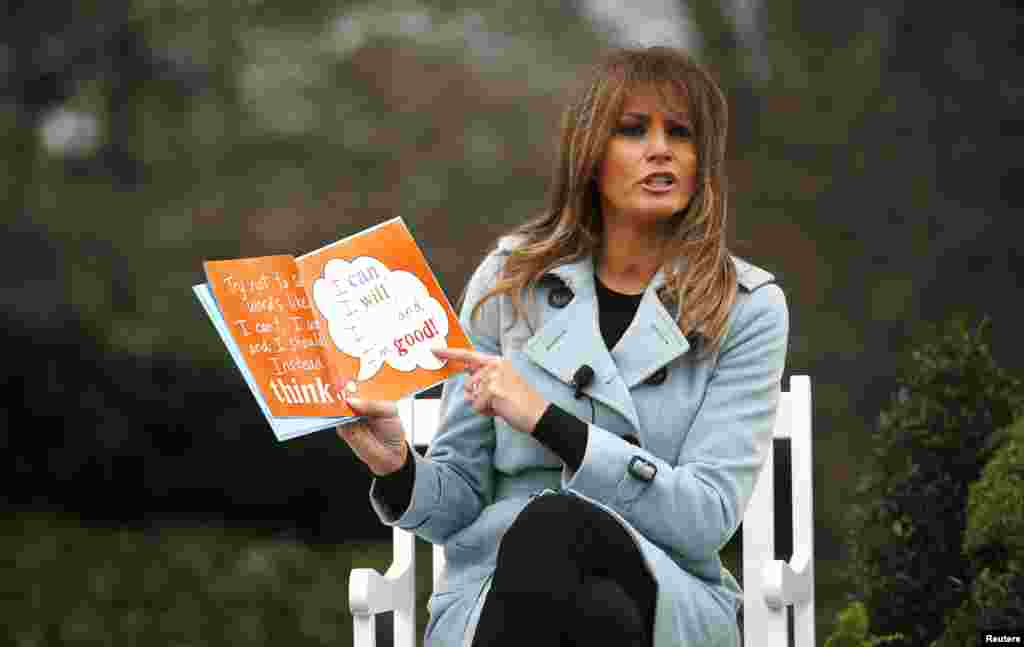 U.S. first lady Melania Trump reads a book to children gathered for the annual White House Easter Egg Roll on the South Lawn of the White House, April 2, 2018.