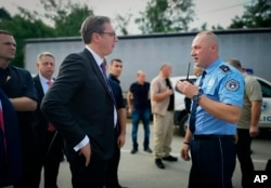 In this photograph made available by the Serbian Presidency, a Kosovo police officer speaks to Serbia's president Aleksandar Vucic, left, to say he cannot continue his trip to the village of Banje due to roadblocks, in Zubin Potok, Kosovo, Sept. 9, 2018.