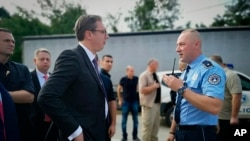 In this photograph made available by the Serbian Presidency, a Kosovo police officer speaks to Serbia's president Aleksandar Vucic, left, to say he cannot continue his trip to the village of Banje due to roadblocks, in Zubin Potok, Sept. 9, 2018.