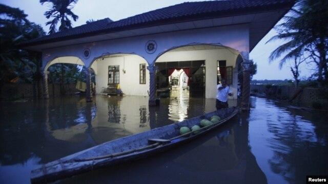 Seorang warga mengikat perahunya di depan rumahnya yang tergenang banjir di Tumpat, 500 kilometer sebelah timur laut Kuala Lumpur (26/12).