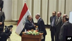 Iraq's President Jalal Talabani, center left, shakes hands with Osama al-Nujeifi, center right, the elected parliament speaker during a Parliament session in Baghdad, Iraq, 11 Nov 2010
