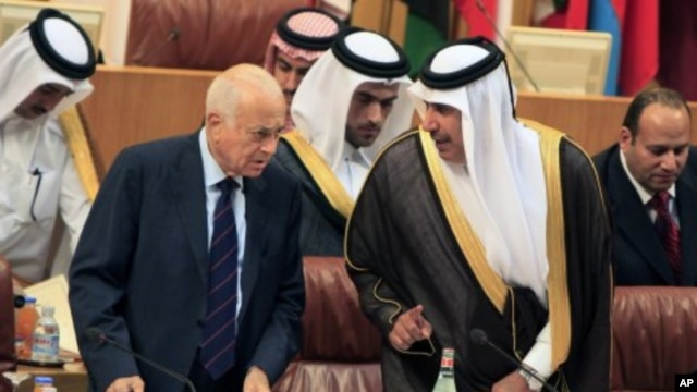 Arab League Secretary-General Nabil al-Arabi, left, talks to Qatari Foreign Minister Sheikh Hamad bin Jassim al- Thani, during an Arab foreign ministers meeting at the Arab League headquarters in Cairo to discuss the possibility of suspending Syria's memb