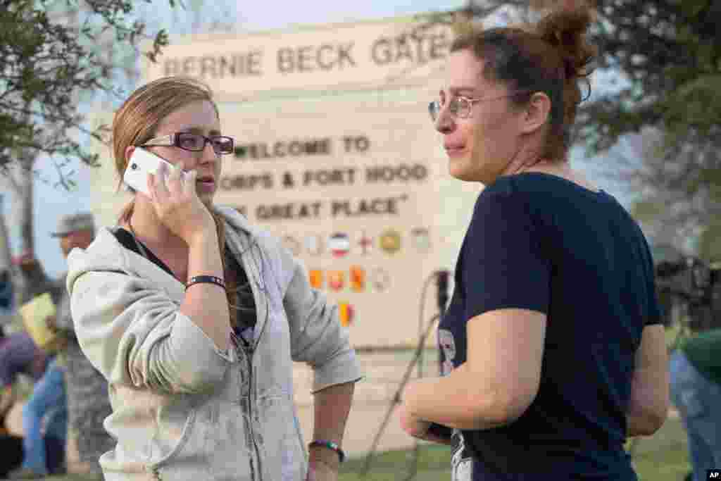 Krystina Cassidy and Dianna Simpson attempt to make contact with their husbands who are stationed inside Fort Hood, while standing outside of the Bernie Beck Gate, April 2, 2014.