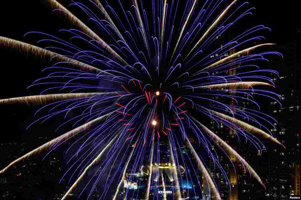 Fireworks explode over Chao Phraya River during the New Year celebrations in Bangkok, Thailand, Jan. 1, 2021.