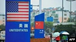 资料照:中国山东青岛商店外的中国和美国国旗。(2018年9月19日)
