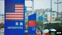 រូបឯកសារ៖ ស្លាកសញ្ញាជាមួយនឹងទង់ជាតិសហរដ្ឋអាមេរិក និងចិននៅខាងក្រៅហាងលក់ទំនិញមួយនៅក្រុង Qingdao ខេត្ត Shandong ប្រទេសចិន កាលពីថ្ងៃទី១៩ ខែកញ្ញា ឆ្នាំ២០២០។