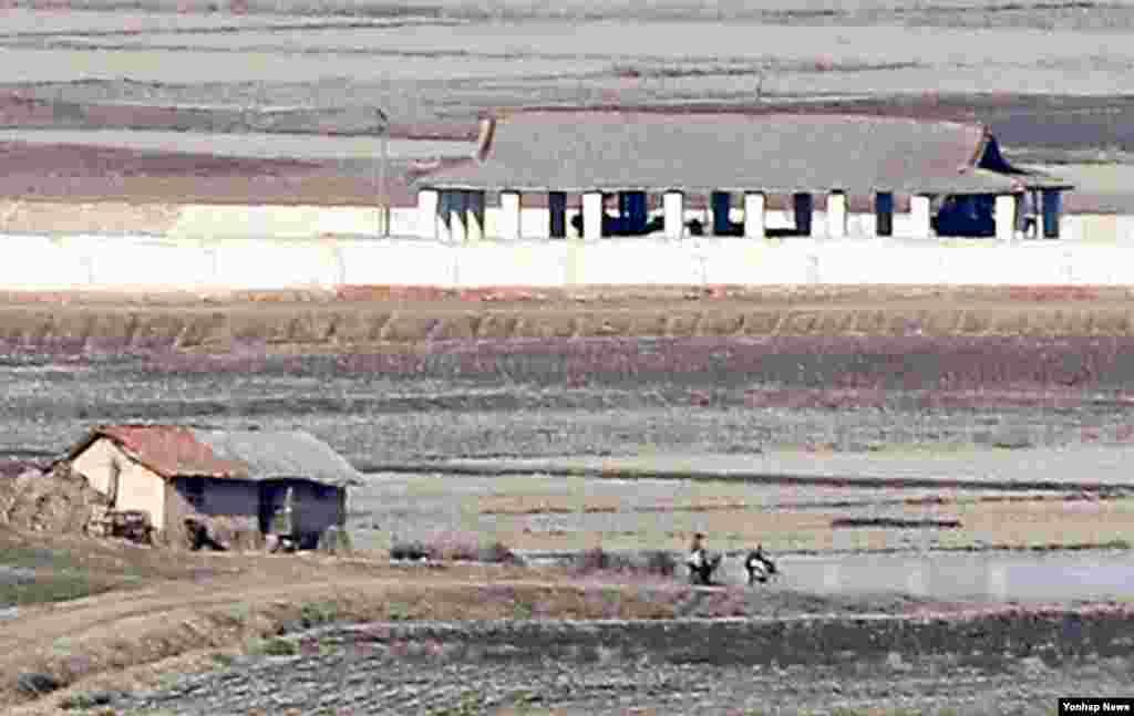 28일 한국의 강화군 평화전망대에서 바라본 북한 개풍군 일대 마을 주민이 자전거를 타고 이동하고 있다.