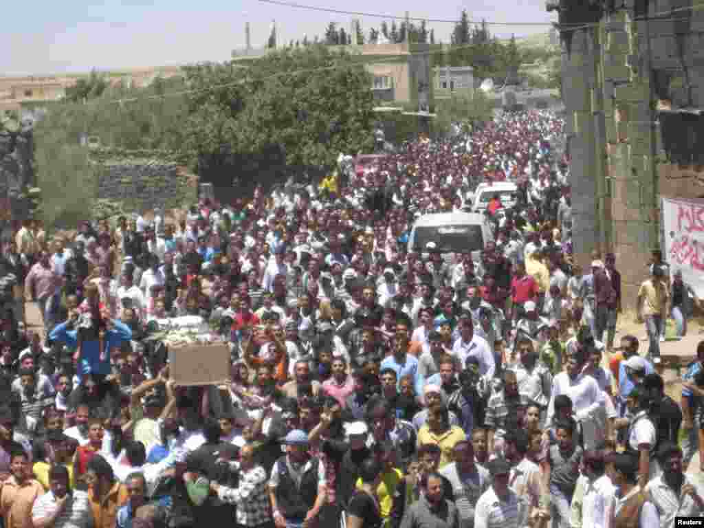 Syrian residents carry the body of Abed Al-Razaq Al-Zubi, whom protesters say was killed by forces loyal to Syria's President Bashar al-Assad, during his funeral in Dara, June 8, 2012.