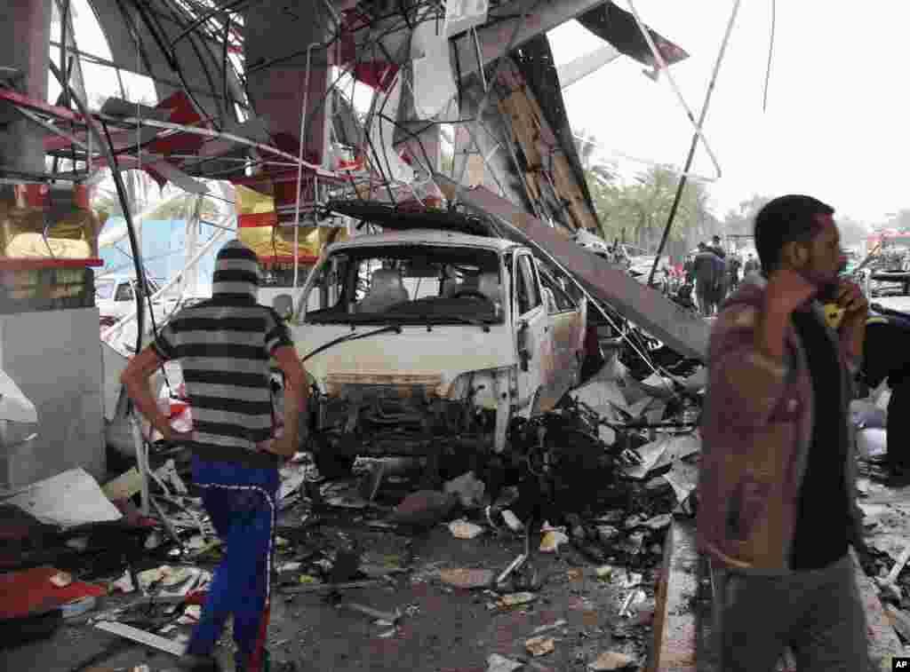 شهروندان غيرنظامی محل انفجار در حله (۹۰کيلومتری جنوب بغداد) را بررسی می کنند. - ۱۸ اسفندماه