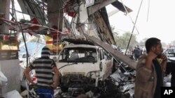 Warga sipil memeriksa lokasi serangan bom di Hillah, 95 kilometer sebelah selatan Baghdad, Irak (9/4).