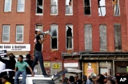 FILE - A protester leads marchers in a chant in front of blighted buildings in Baltimore, Maryland, May 2, 2015.
