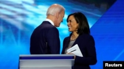 FILE PHOTO: Former Vice President Joe Biden talks with Senator Kamala Harris after the conclusion of the 2020 Democratic U.S. presidential debate in Houston, Texas, U.S., September 12, 2019. REUTERS/Mike Blake/File Photo
