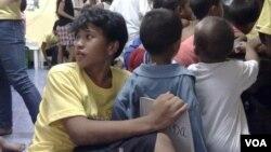 Kesz ngồi đằng sau một cậu bé 5 tuổi lắng nghe một bài học. Kesz bị bỏng nặng hồi 8 năm trước tại một bãi rác ở gần thủ đô Manila