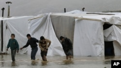 Syrian refugee boys make their way in flooded water at a temporary refugee camp in the Lebanese town of Al-Faour, near the border with Syria, January 8, 2013.