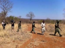Some of Mander's rangers on patrol with an American television crew in a wildlife park in Zimbabwe