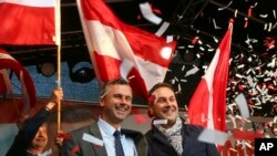 FILE - In this May 20, 2016 file photo Norbert Hofer candidate for presidential elections of Austria's Freedom Party, FPOE, and Heinz-Christian Strache, from left, head of Austria's Freedom Party, FPOE, look out at supporters during the final election cam
