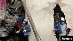 "Warga dan regu penolong berupaya melakuka pencaraian korban di balik reruntuhan bangunan Rana Plaza di Savar, 30 kilometer di luar Dhaka (26/4). Pihak berwenang telah menangkap dua orang pemimpin pabrik garmen ""New Wave Apparels"", Sabtu (27/4)."