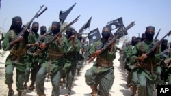 Al-Shabab fighters march with their weapons during military exercises on the outskirts of Mogadishu, Somalia.