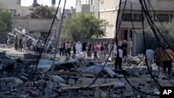 Người dân Palestine kiểm tra thiệt hại một nhà máy sản xuất sữa bị phá hủy bởi một cuộc không kích của Israel tại Dải Gaza, ngày 31/7/2014.