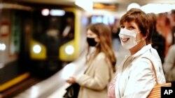 На фото: люди у захисних масках на платформі метро у Берліні