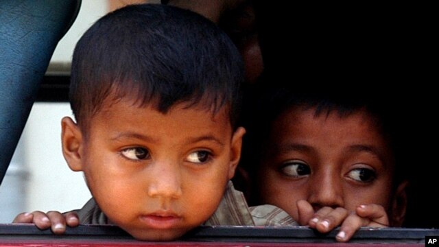 Rohingya minority children look out through a window of a bus after they were rescued by Thai authorities in Songkhla province, southern Thailand, Jan. 11, 2013.  Nearly 700 boat people from Myanmar's beleaguered Rohingya minority were rescued from alleged human traffickers in two separate raids near Thailand's southern border.