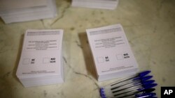 Ballots ready to be used by voters sit on a table at a sports center assigned to be a polling station by the Catalan government and where Catalan President Carles Puigdemont is expected to vote, in Sant Julia de Ramis, near Girona, Spain, Oct. 1, 2017.