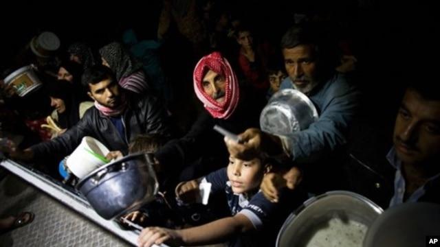 지난달 23일 시리아 아자즈 지역의 난민캠프에 구호 식량을 수급받는 피난민들.