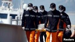 Rescatistas cargan el cadaver de otro estudiante recuperado del ferry Sewol, que se hundió la semana pasada en Corea del Sur.