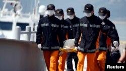 Para petugas penyelamat menggotong jenazah para penmupang kapal Sewol yang tenggelam di pelabuhan Jindo (20/4). (Reuters/Kim Hong-Ji)