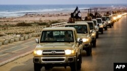 An image made available by propaganda Islamist media outlet allegedly shows members of the Islamic State parading in a street in Sirte, Libya.
