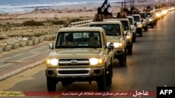 FILE - An image made available by propaganda Islamist media outlet Welayat Tarablos on Feb. 18, 2015, allegedly shows members of the Islamic State (IS) militant group parading in a street in Libya's coastal city of Sirte, which lies 500 kilometers (310 miles) east of the capital, Tripoli.