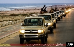 FILE - An image made available by propaganda Islamist media outlet Welayat Tarablos on Feb. 18, 2015, allegedly shows members of the Islamic State militant group parading in a street in Libya's coastal city of Sirte, which is 500 kilometers (310 miles) east of the capital, Tripoli.