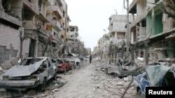 Mobil-mobil dan bangunan-bangunan yang hancur terlihat di kota Douma, Ghouta Timur, Damaskus, Suriah yang terkepung, 25 Februari 2018.