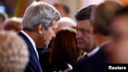 El secretario de Estado de EE.UU., John Kerry (Izquierda) conversa con el presidente electo de Ucrania Petro Poroshenko, en un encuentro en Polonia, en donde también está de visita oficial el presidente Barack Obama.